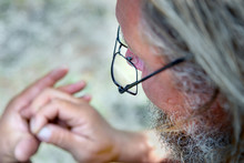 An Old Man With A Beard And Glasses Looks At His Hands. Concept Of Old Age And Poor Vision