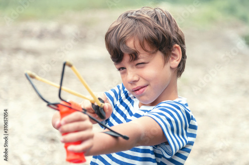 A boy in a striped T-shirt shoots a slingshot, front view Tablou Canvas