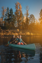 Happy Couple In Canoe At Sunset.