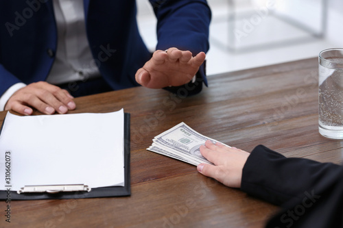 Fotografía  Businessman refuses to take bribe money at wooden table, closeup
