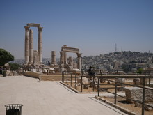 Roman Ruins Of The Citadel Of Amman, Capitol Of Jordan, Remains Of A City Build From Stone And Tall Pillars On A Brown Hill In The Middle Of A City