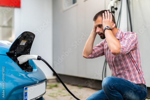 Leinwand Poster Handsome young man plugging cable to electric car with hands on head shocked