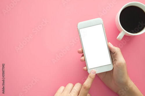 Mockup image of hands holding white mobile phone with blank white .screen with Modern pink office desk with laptop and other supplies for input the text on copy space Top view, flat lay.