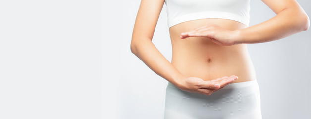Close up woman hands made protect shape stomach isolated on white background banner size.health care digesting concept.