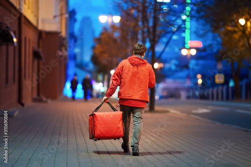 Fényképezés Young deliveryboy walking with red thermal bag on night city street