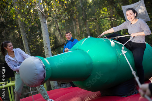Woman having fun on inflatable rodeo bottle Canvas Print