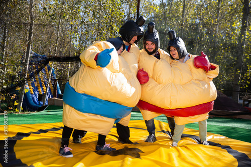Fotomural Friends posing in inflatable sumo suits