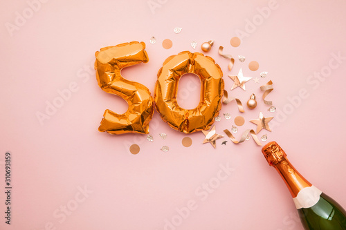 Happy 50th anniversary party. Champagne bottle with gold number balloon.