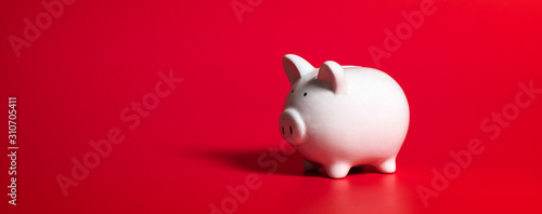 Stampa su Tela Composition with piggy bank isolated on red background.