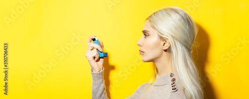 Fotografie, Tablou Studio portrait of young blonde girl holding asthmatic inhalator on yellow background with copy space