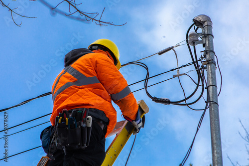 Obraz na plátne A telecoms operative is seen working from a ladder on a utility pole, wearing hi