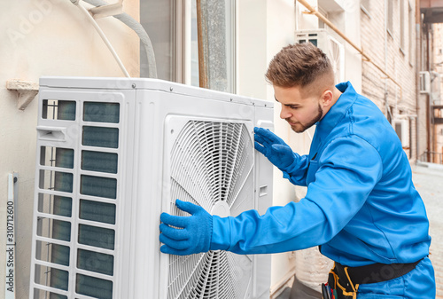mata magnetyczna Male technician installing outdoor unit of air conditioner