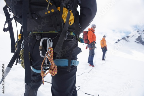 Photo Backpack And Safety Ropes In Snowy Mountains With Two Friends Ahead