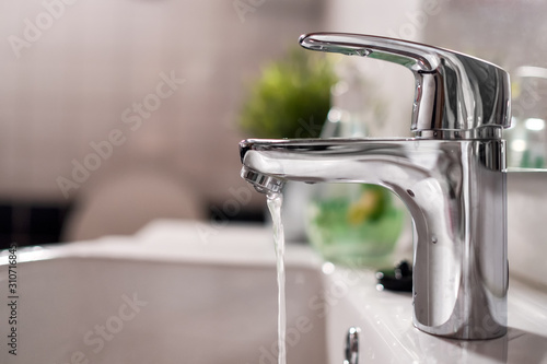 Canvastavla Cold water flowing from faucet in clean bright bathroom