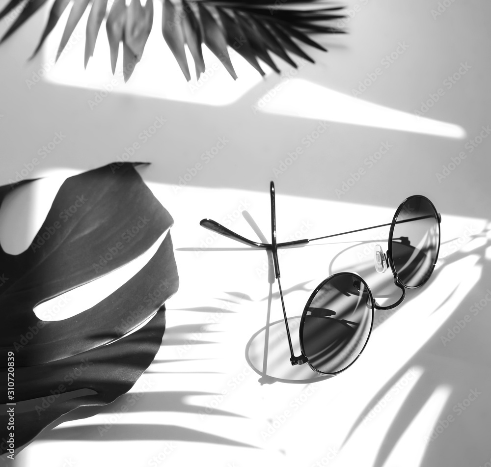 Fototapeta Fashion creative composition with women's sunglasses and tropical palm, monstera leaves black and white color on white background with floral shadow.  Flat lay, top view . copy space