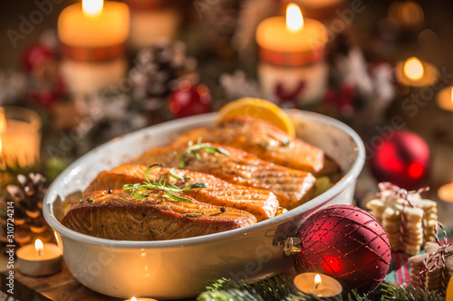 Fototapeta Christmas dinner from fish salmon in roasting dish with festive decoration advent wreath and candles. obraz