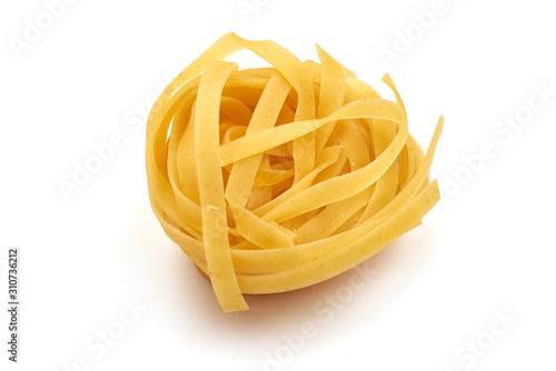 Fotografia  Raw tagliatelle pasta, isolated on white background