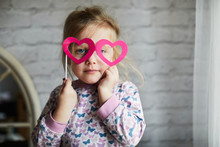 Child Playing With Heart Glasses