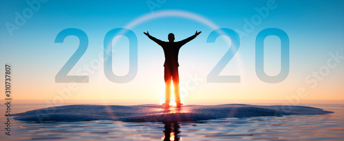Silhouette of a man and 2020 concept in beautiful sunset sky and sea background