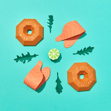 Handcraft Paper Half-buns, Pieces Of Red Fish And Arugula Leaves And Lime On A Blue Background With Copy Space. Healthy Burger. Flat Lay