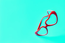 Red Glasses In Lenses In The Shape Of Hearts On A Blue Turquoise Background. The Concept Of Good Vision, Love And Valentine's Day. Vertical Composition. Love At First Sight. Space For Design Text