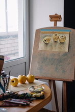 Easel With Drawing Of Yellow Apples In The Studio