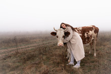 Beautiful Brunette Girl In White Coat Stands Among The Meadow In Fog With Red And White Coe, Hugging Her And Looking At The Camera