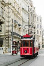 Tram Driving On Street Between Vintage Buildings