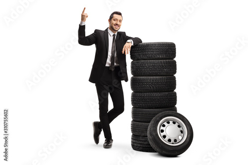 Fotografía Young businessman pointing above and leaning on a pile of car tires