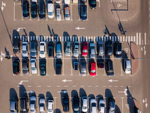 Top Aerial View Parking Lot With Road Marking, Colored Cars And Long Shadows On A Gray Background. Bird's Eye View From Drone.