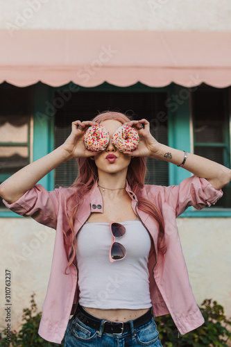 Woman holding donuts over her eyes puckering her lips