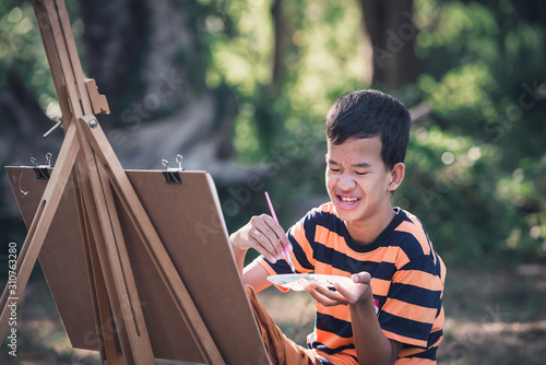Asian boy with Down's syndrome is happily drawing a picture of an elephant in the garden Fototapet