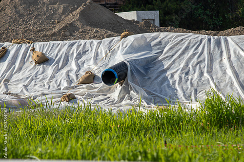 plastic sheeting laying over dirt in city construction along hillside Fototapeta