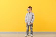 Portrait Of Stylish Little Boy Against Color Wall