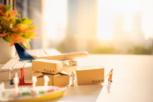 Miniature People: Worker And Brown Paper Box, White Keyboard On Blurred City With Airplane, Ship Using As Background Business Shipping, Rent Container, Worldwide Transportation Concept.
