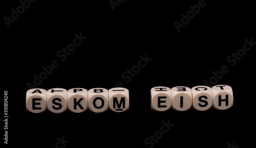 Photo The term Eskom and the South African slang word eish aghast isolated on a black