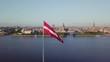 Latvian flag with Riga panorama behind
