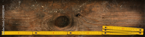 Fototapeta Close-up of a yellow wooden folding ruler on a work table with copy space and da