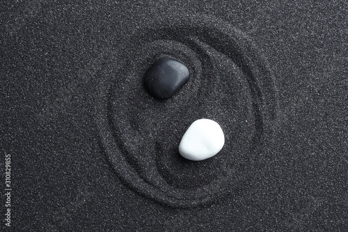 Yin Yang symbol made with stones on black sand, top view. Zen concept