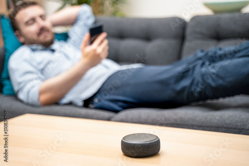 Obraz Man using home assistant bluetooth speaker - fototapety do salonu