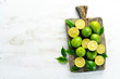 Green limes on white wooden background. Fruits. Top view. Free space for your text.