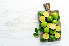 Green Limes On White Wooden Ba...
