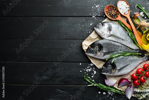 Fototapeta Raw dorado fish with lemon and spices on a black background. Top view. Free space for your text. obraz