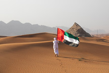 Arab Man Holding The UAE Flag In The Desert Celebrating UAE National Day And Uae Flag Day.
