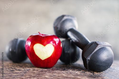 Fotografia red apple with dumbbells , sport diet ,heart healthy concept
