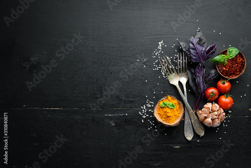 Fototapeta The background of cooking. On a black wooden background. Top view. Free space for your text. obraz