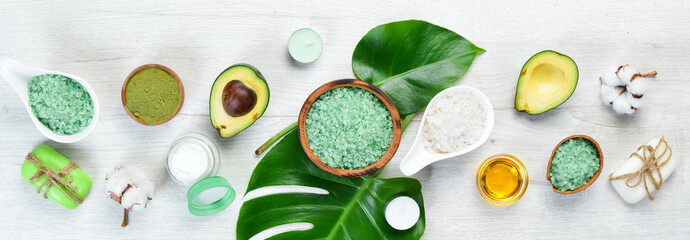Cosmetics from avocado, avocado oil, sea salt and face cream, on a white wood...