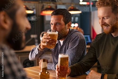 Fotomural  Man drinking draft beer with friends