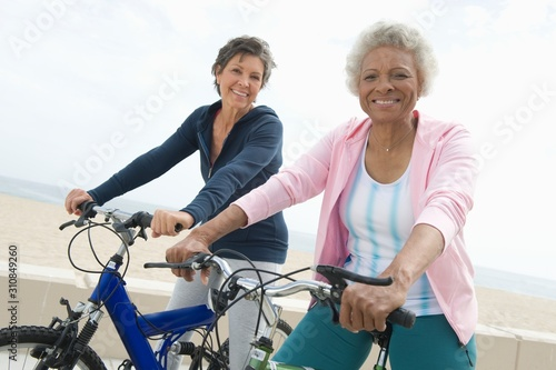 Portrait of happy senior multiethnic female friends riding bicycles together Wallpaper Mural