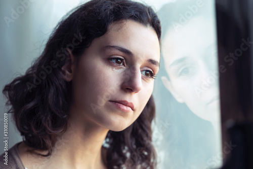 Photo Sad young woman crying while looking through the window at home.